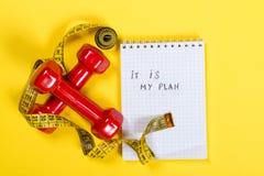 红色哑铃和测量的磁带和文本-它是我的在纸的计划 概念健康生活方式 免版税库存图片