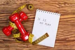 红色哑铃和测量的磁带和文本-它是我的在纸的计划 概念健康生活方式 库存图片