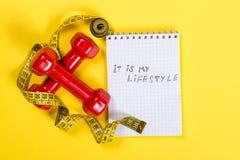 红色哑铃和测量的磁带和文本-它是我的在纸的lifeslyle- 概念健康生活方式 库存照片