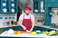红色围裙的厨师由在切板的陶瓷刀子切开菜 免版税库存图片