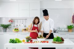 红色围裙的美丽的亚裔妇女学会如何的烹调和混合 库存照片