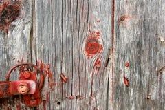 红色土气与门闩硬件的谷仓木背景 库存图片
