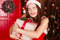 红色圣诞老人坐在ne附近的帽子和红色礼服的年轻愉快的妇女 库存图片