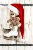 红色圣诞老人帽子、玩具熊和白色滑冰 库存照片