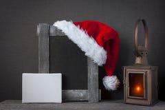 红色圣诞老人帽子和一个老木制框架 库存照片