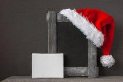 红色圣诞老人帽子和一个老木制框架 免版税库存照片