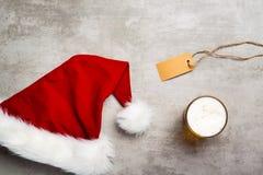 红色圣诞老人帽子和一杯在一张具体桌上的啤酒 库存图片