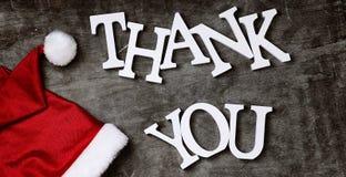 红色圣诞老人帽子和信件感谢您灰色被构造的木后面的 免版税图库摄影