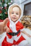红色圣诞老人帽子和礼服的逗人喜爱的愉快的女婴 库存照片