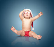 红色圣诞老人帽子和红色玻璃的小逗人喜爱的婴孩 免版税库存图片