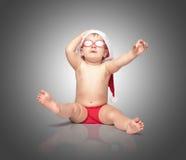 红色圣诞老人帽子和红色玻璃的小逗人喜爱的婴孩 库存照片