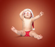 红色圣诞老人帽子和红色玻璃的小逗人喜爱的婴孩 免版税图库摄影