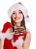 红色圣诞老人帽子的圣诞节女孩吃在板材的蛋糕。 免版税库存图片