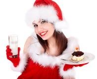 红色圣诞老人帽子的女孩吃在板材的蛋糕。 免版税库存照片