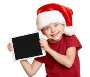 红色圣诞老人帽子的女孩有在白色的片剂个人计算机的被隔绝的 免版税库存图片