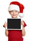 红色圣诞老人帽子的女孩有在白色的片剂个人计算机的被隔绝的 库存照片