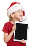 红色圣诞老人帽子的女孩有在白色的片剂个人计算机的被隔绝的 免版税库存照片