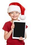 红色圣诞老人帽子的女孩有在白色的片剂个人计算机的被隔绝的 库存图片
