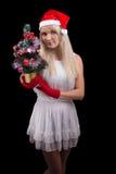 红色圣诞老人帽子的女孩有Cristmass结构树的 免版税库存照片