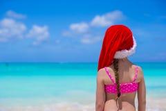 红色圣诞老人帽子的小可爱的女孩享用海滩 库存图片