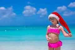 红色圣诞老人帽子的小可爱的女孩享用海滩 免版税库存图片