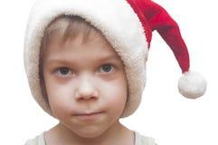 红色圣诞老人帽子的小男孩 免版税库存图片