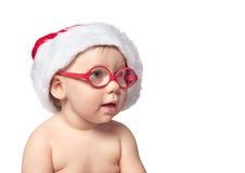 红色圣诞老人帽子的小逗人喜爱的婴孩在颜色bacground 免版税库存照片