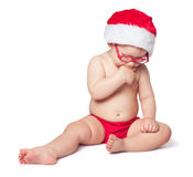 红色圣诞老人帽子的小逗人喜爱的婴孩 免版税库存照片