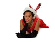 红色圣诞老人帽子的微笑的妇女 免版税库存图片