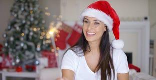 红色圣诞老人帽子的欢乐的少妇 库存照片