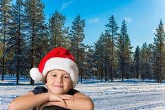 红色圣诞老人帽子的男孩微笑着 免版税库存图片