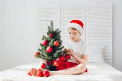 红色圣诞老人帽子的男孩装饰一棵小圣诞树球 免版税图库摄影
