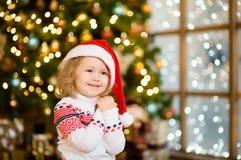 红色圣诞老人帽子的逗人喜爱的小女孩 免版税库存图片