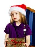 红色圣诞老人帽子的逗人喜爱的矮小的学龄前儿童女孩有礼物盒的 免版税库存图片