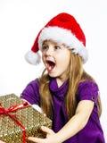 红色圣诞老人帽子的逗人喜爱的矮小的学龄前儿童女孩有礼物盒的 免版税图库摄影