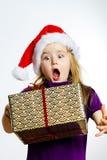 红色圣诞老人帽子的逗人喜爱的矮小的学龄前儿童女孩有礼物盒的 库存照片