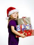 红色圣诞老人帽子的逗人喜爱的矮小的学龄前儿童女孩有礼物盒的 库存图片