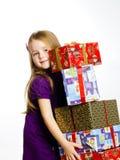 红色圣诞老人帽子的逗人喜爱的矮小的学龄前儿童女孩有礼物盒的 图库摄影