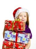 红色圣诞老人帽子的逗人喜爱的矮小的学龄前儿童女孩有礼物盒的 免版税库存照片