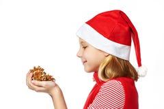红色圣诞老人帽子的Beautyful女孩有金黄杉木锥体的 免版税库存图片