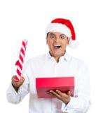 戴红色圣诞老人帽子,衬衣的英俊的年轻人,打开的礼物和愉快 免版税库存图片