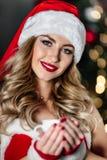 红色圣诞老人服装的性感的年轻白肤金发的妇女有红色鞋子和白色茶的咖啡微笑 免版税库存照片