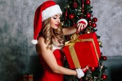 红色圣诞老人服装的性感的年轻白肤金发的妇女有红色鞋子和白色茶的咖啡微笑 免版税库存图片