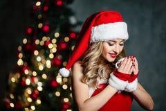 红色圣诞老人服装的美丽的性感的白肤金发的女孩在白色长袜红色鞋子微笑在圣诞树附近的 免版税库存图片