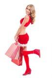 红色圣诞老人的愉快的beautyful妇女穿衣与购物袋 免版税图库摄影