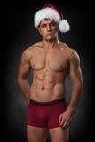 红色圣诞老人盖帽的肌肉人在黑暗的背景 免版税库存照片