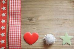 红色圣诞节丝带、一个蓬松球、星和爱心脏 免版税库存图片