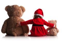 红色圣诞节圣诞老人帽子的小女孩拿着他的玩具熊玩具朋友 概念新年度 库存图片