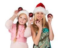 红色圣诞节帽子的两个女孩在韩拿着红色冷杉木球形 免版税库存照片