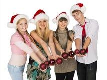红色圣诞节帽子的四个微笑的少年有冷杉木spher的 免版税图库摄影
